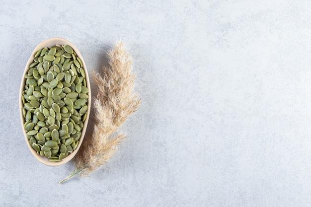 Ciotola beige di semi di zucca sbucciati su fondo di pietra.
