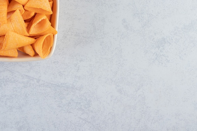 Beige bowl of triangle shaped crispy chips on stone background.