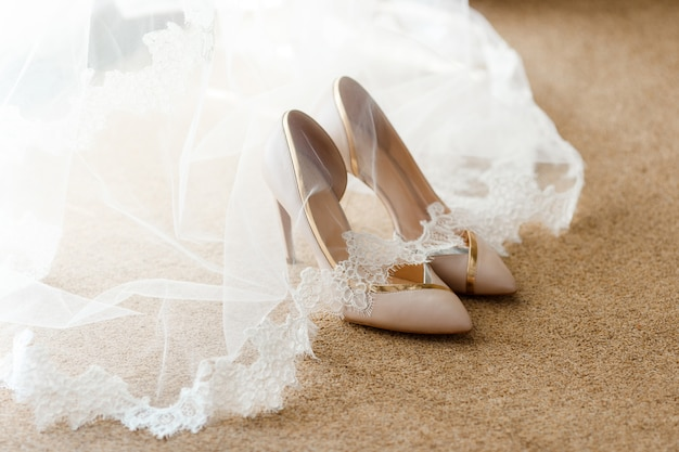 Beige bridal shoes standing on the floor, covered with a veil with lace