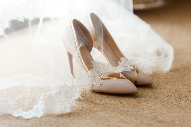 Beige bridal shoes standing on the floor, covered with a white veil with lace