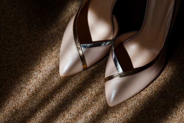 Beige bridal shoes standing on the floor and shining on the sun rays