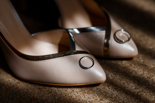 Beige bridal shoes standing on the floor, with a gold rings