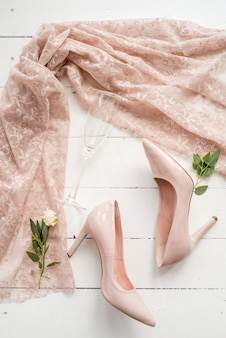 Beige bride shoes and other accessories are covered the veil.