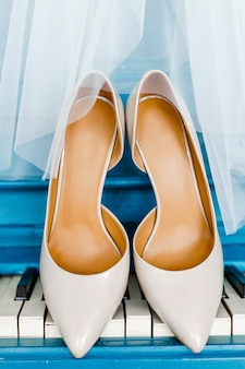 Бежевые туфли невесты, стоящие на пианино, прикрытые белой вуалью
