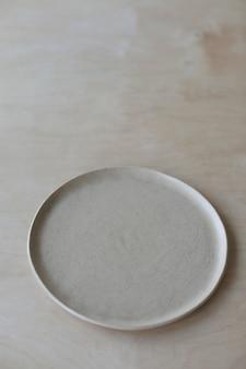 Бежевая керамическая тарелка на деревянном столе. минималистская керамическая посуда и керамика ручной работы