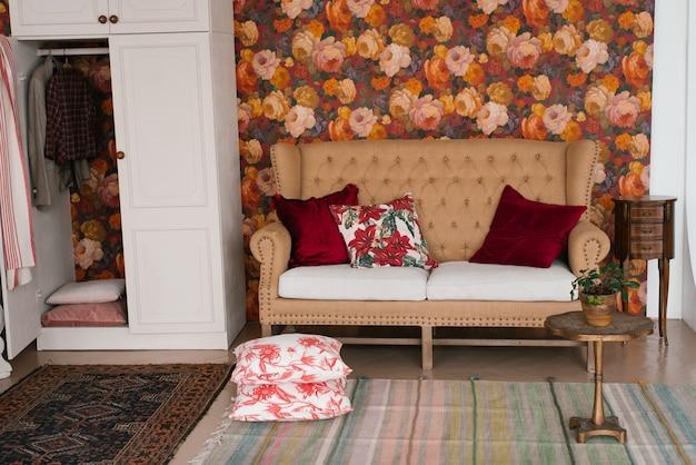 Бежевый классический диван с яркими подушками и белым шкафом в спальне или гостиной