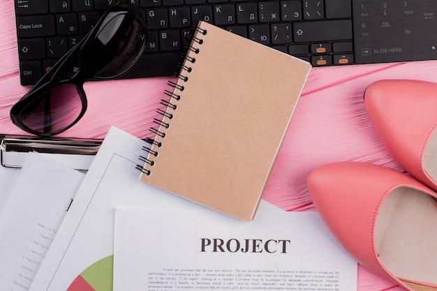 ピンクの机の上にファッションの女性のアクセサリーサングラス靴とベージュの閉じたスパイラルメモ帳