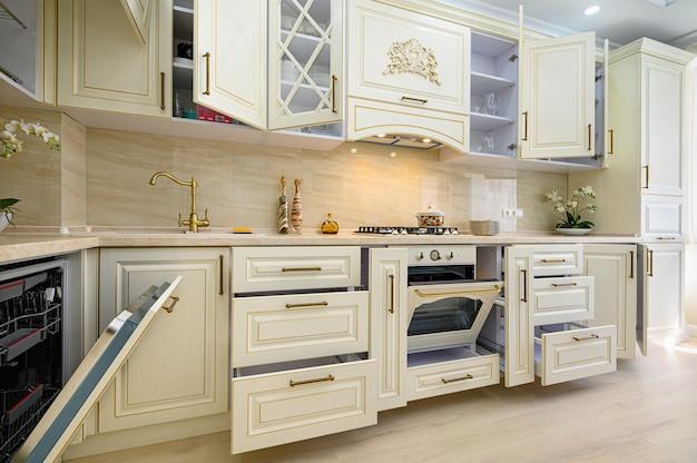 Современная классическая кухня бежевого цвета в интерьере в стиле прованс, вся мебель с открытыми дверцами и ящиками.