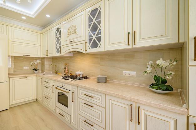 Интерьер современной классической кухни бежевого цвета в стиле прованс, угол к фасаду.