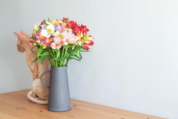 Бежевая корнишская кошка с букетом цветов в вазе на деревянном столе