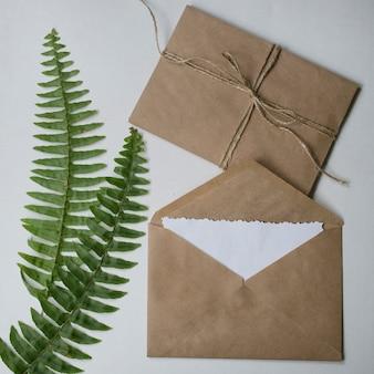 베이지 색 공예 봉투, 흰색 빈 메모 카드 및 녹색 열대 나뭇잎.