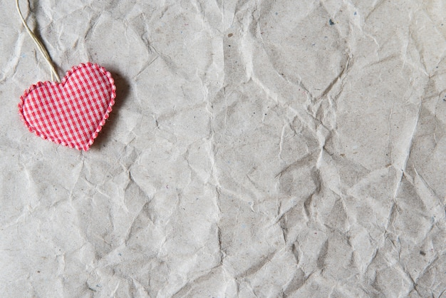 Beige crumpled paper with pink heart for valentine, love and wedding background.