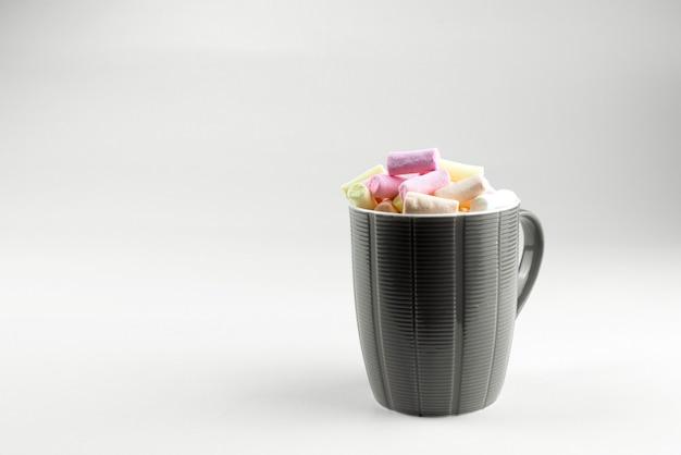 明るい背景にココアとマルチカラーのマシュマロとベージュのカップ。
