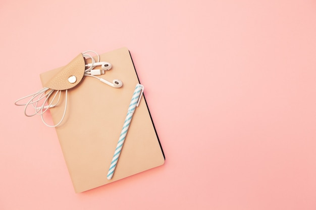 Beige diary with blue pen and headphones on pastel millennial pink paper background.