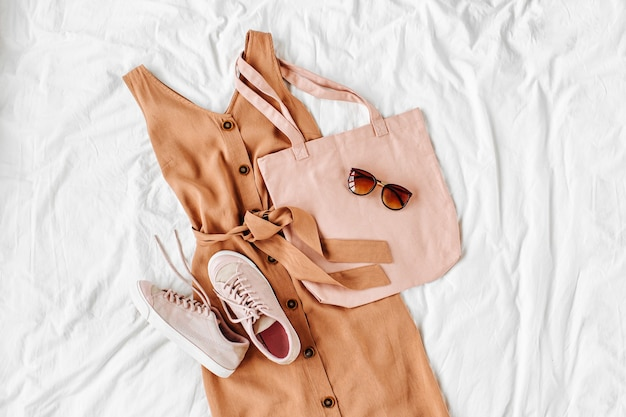 白いベッドの上にエコバッグ、スニーカー、アクセサリーが付いたベージュのドレス。女性のスタイリッシュな秋または夏の衣装。流行りの服。フラットレイ、上面図。
