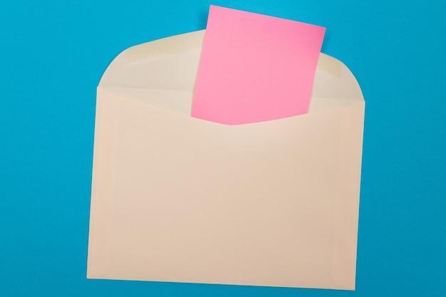 Бежевый конверт с пустым розовым листом бумаги внутри