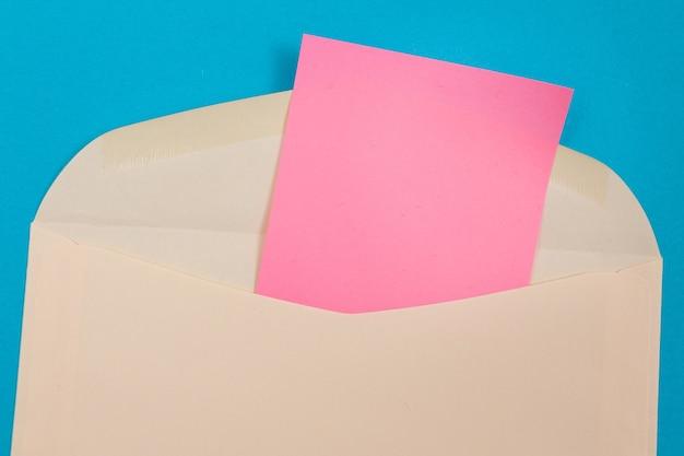 内側に空白のピンクの紙が入ったベージュの封筒