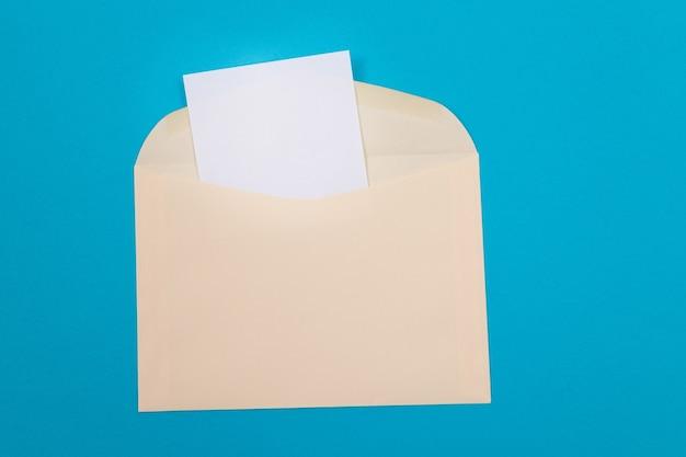 Бежевый конверт с чистым белым листом бумаги внутри, лежащим на синем фоне, макет с копией ...