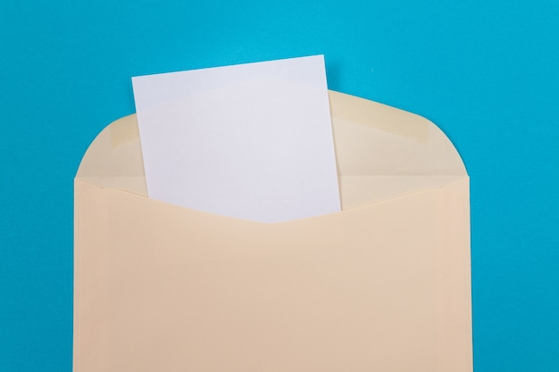 Бежевый конверт с чистым белым листом бумаги внутри
