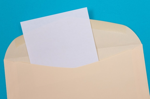 Beige envelope with blank white sheet of paper inside