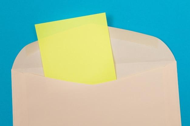 Бежевый конверт с пустым желтым листом бумаги внутри