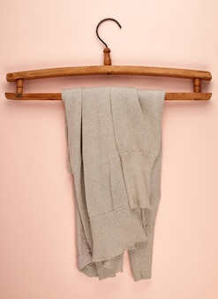 Beige female sweater hanging on a vintage wooden hanger