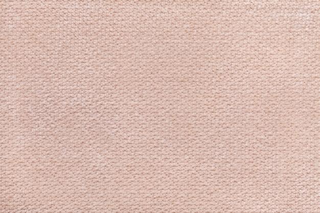 柔らかく、フリースの布のベージュのふわふわの背景。繊維のクローズアップのテクスチャ