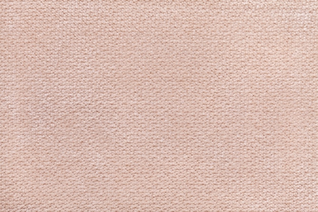 Beige fluffy background of soft, fleecy cloth. texture of textile closeup
