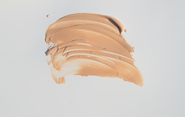 Beige foundation for make-up, cosmetic touches on white background
