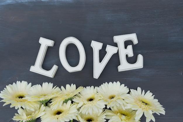 ベージュのガーベラの花がラブレターでダークウッドに縁取られています