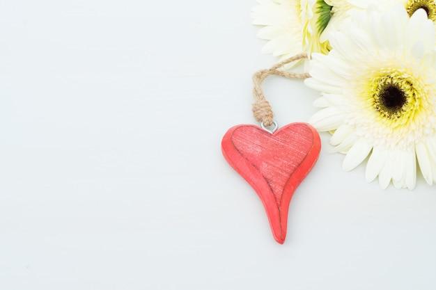 灰色の木製テーブルの上のバレンタインデーのための赤いハートとベージュのガーベラの花