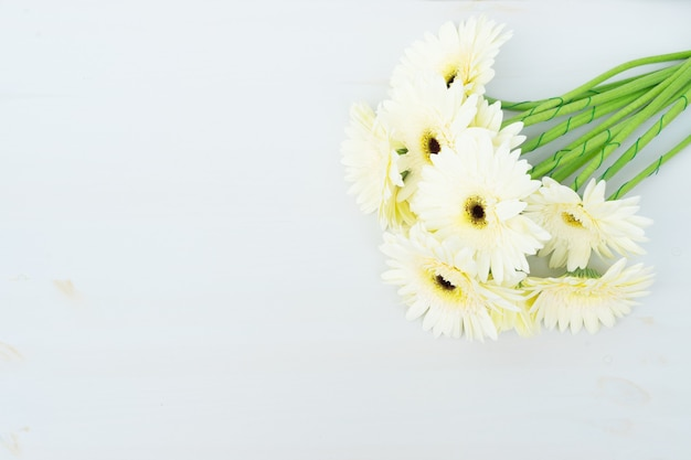 Beige gerbera flowers on wooden table with copy space