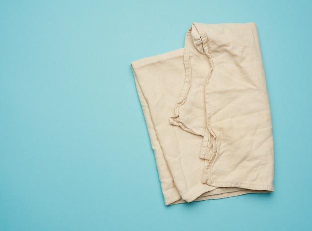 파란색에 접힌 베이지 색 주방 섬유 수건