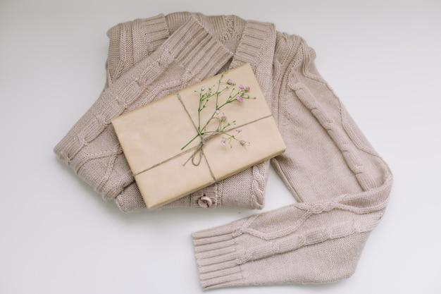 Бежевый вязаный свитер с подарком из крафт-бумаги, вид сверху с copyspace