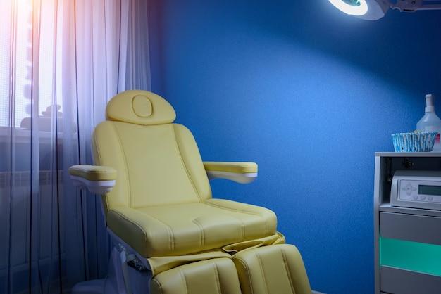 ベージュレザーペディキュアアームチェアのクローズアップ。ブルーの色調の化粧品キャビネット。スパサロンの家具。