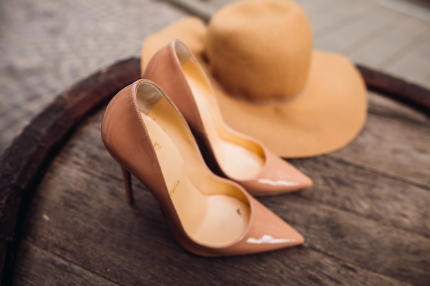 Beige luis vuitton shoes and hat lie on the barrel