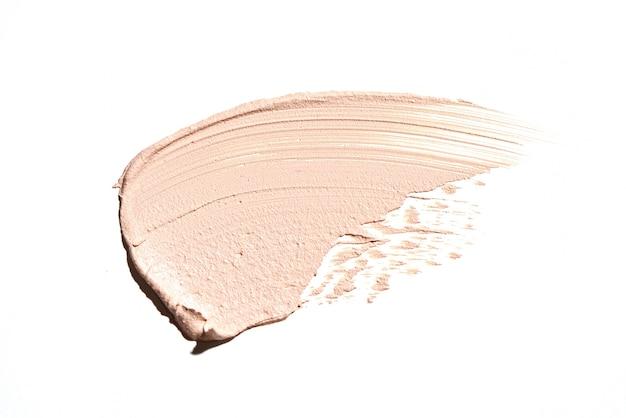 白い背景に分離されたベージュのメイクアップクリーミーなファンデーション塗抹標本。肌の化粧品見本、ライトブラウンクリームのブラシストローク。フェイスブロンザー製品またはbbファンデーションの汚れの質感