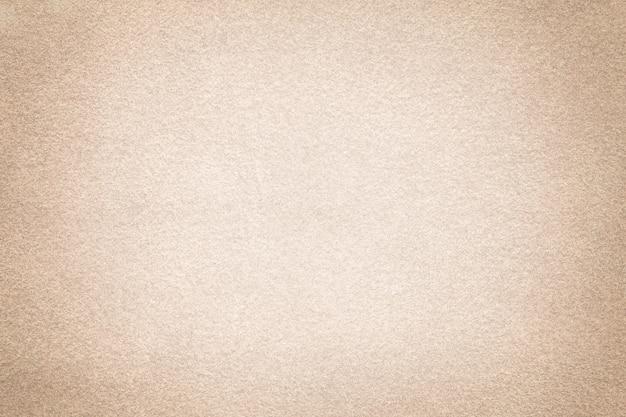비 네트와 스웨이드 원단의 베이지 무광택 배경. 모래의 벨벳 텍스처는 그라디언트로 섬유를 느꼈다.