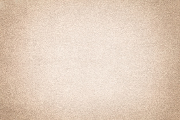 Beige matte background of suede fabric with vignette. velvet texture of sand felt textile with gradient