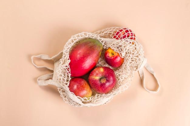 베이지색 배경에 붉은 과일이 있는 베이지색 메쉬 끈 가방.