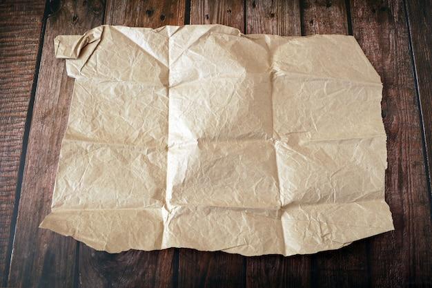 Бежевые морщины старой бумаги на деревянных фоне, крупным планом
