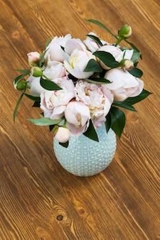 Бежевые пионы в вазе на деревянном столе