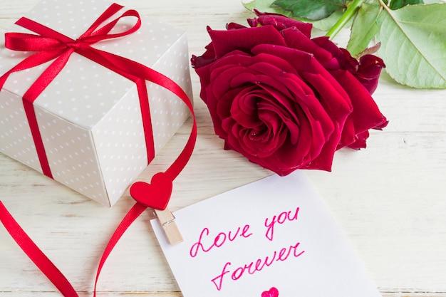 Бежевый горошек подарочная коробка с красной лентой лук и красивые красные розы на деревянных фоне. открытка на праздник.