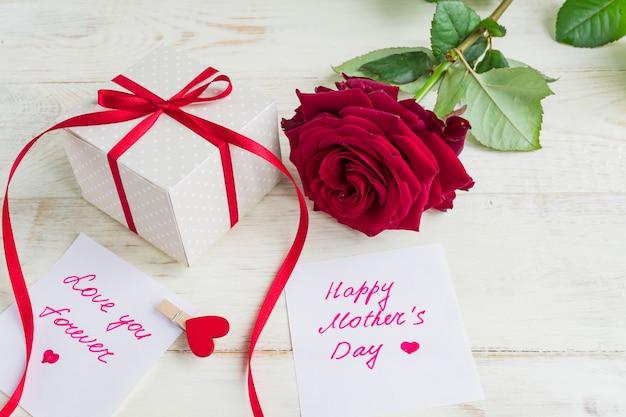 Бежевый горошек подарочная коробка с красной лентой лук и красивые красные розы на деревянных фоне. открытка на день матери