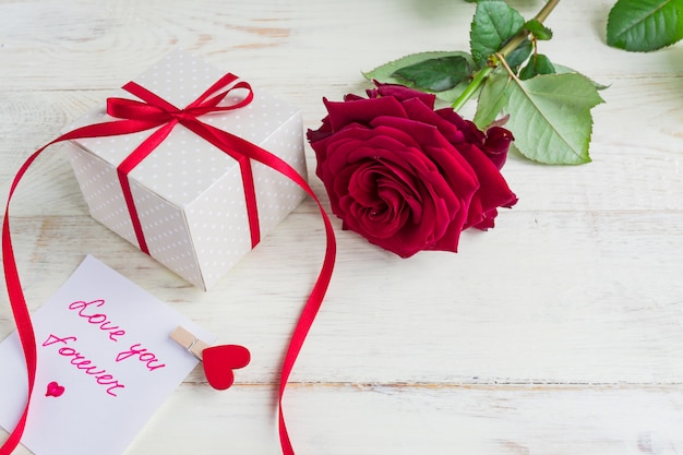 Beige polka dot gift box with red ribbon bow and bautiful red roses on wooden background. greeting card for holiday.