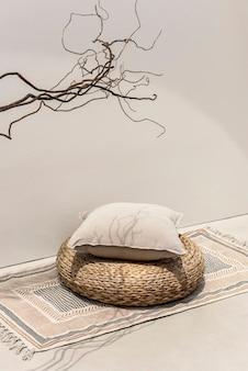 Бежевая подушка с принтом на ротанговом табурете - дизайн интерьера