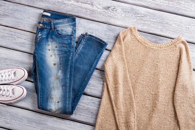 베이지색 풀오버와 청바지 흰색 캔버스 신발과 스웨트셔츠 캐주얼 의류 아울렛 매장 품질...