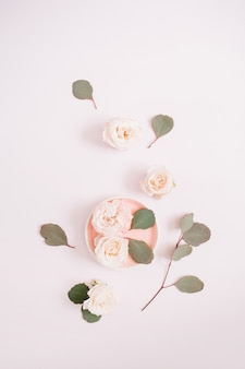 Бежевые розы и ветви эвкалипта на бледно-пастельно-розовом