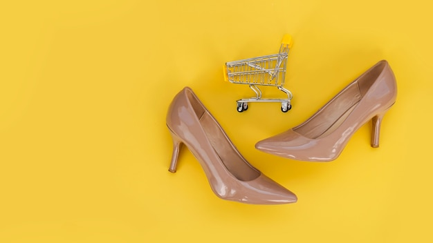 Beige shoes and a shopping cart on a yellow background