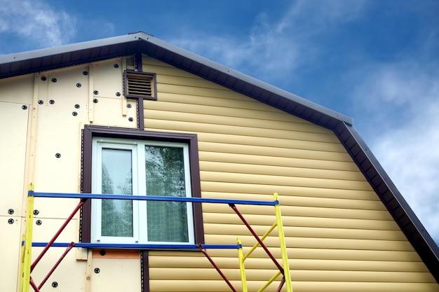 Монтаж бежевых сайдинговых панелей с лесами на сельский дом